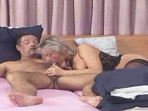 Lewd granny in glasses throats strong cock in bed