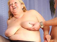 Chubby mature blonde with big tits is fucked from behind while sucking on a dick